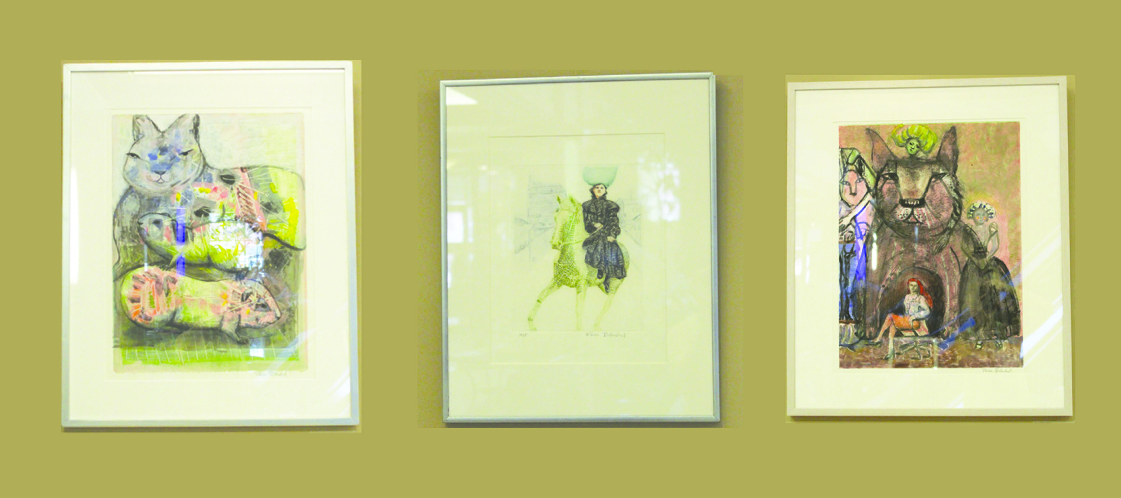Artwork by Paula Bullwinkel displayed in the Franklin Crossing Atrium. Right: Family, Monotype with mixed-media. Center: Annie Rides, Etching. Left: Cat Cave, Monotype with mixed-media.
