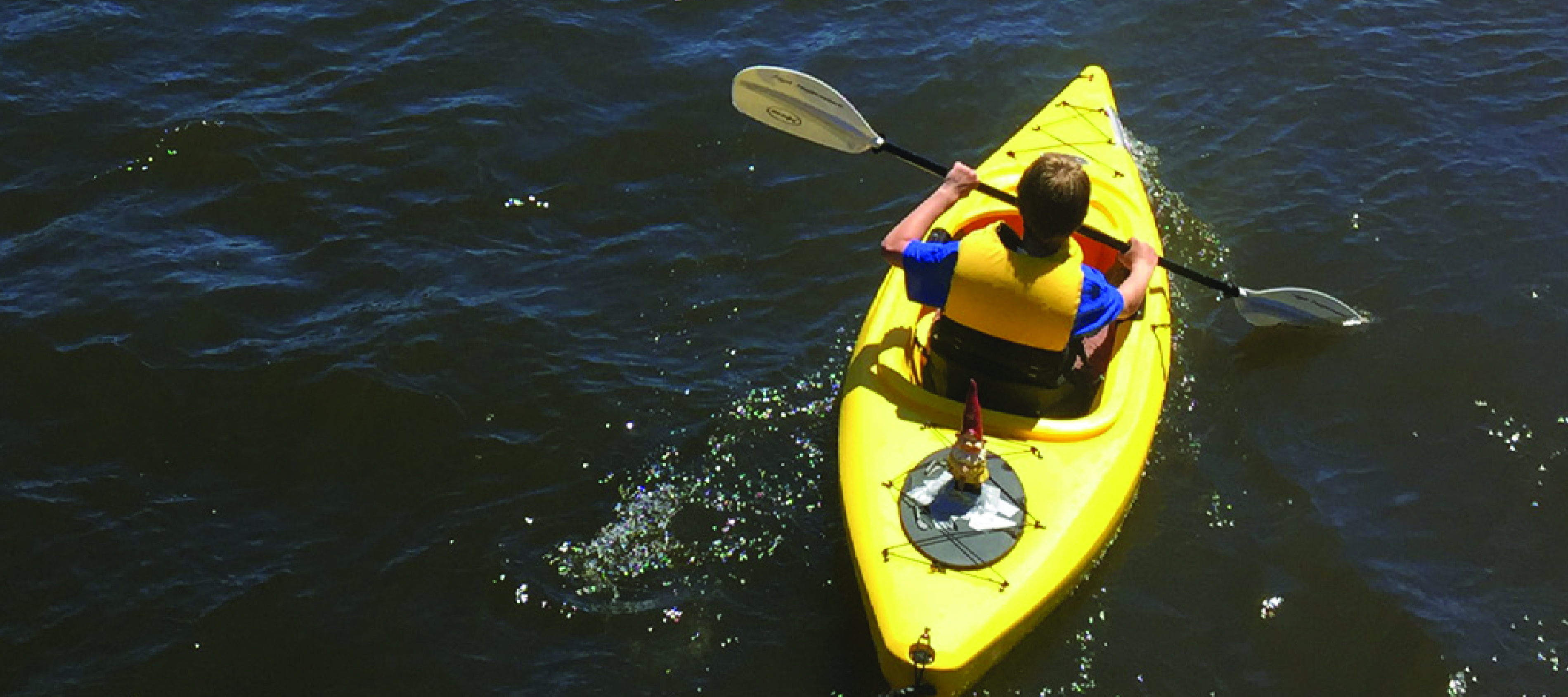 A paddler makes his way down the Deschutes River in a kayak adorned with a smiling garden gnome.