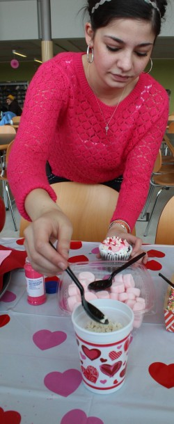 Kayla Miller, ASCOCC Director of Student Activities, helps out with cupcake decorating.  Photo by Vera Holiday | The Broadside.
