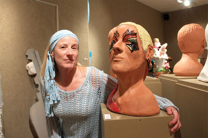 """Sherry Woodyard, sculpture 1 student said that she chose to paint a butterfly mask on her sculpted head in remembrance of her friend Mel Nelson who recently passed and asked her to do an art piece on his instrumental song, """"Rainbow."""""""