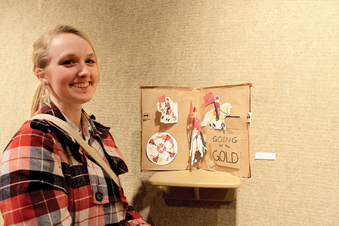 """Amanda Blair, Sculpture 1, shows off her pop-up project, """"Going for the Gold."""" Blair based her project off her equestrian team experience while she attended Redmond High and described that they were the state champions in 2013. Blair is now studying towards a bachelor in fine arts at OSU-Cascades."""