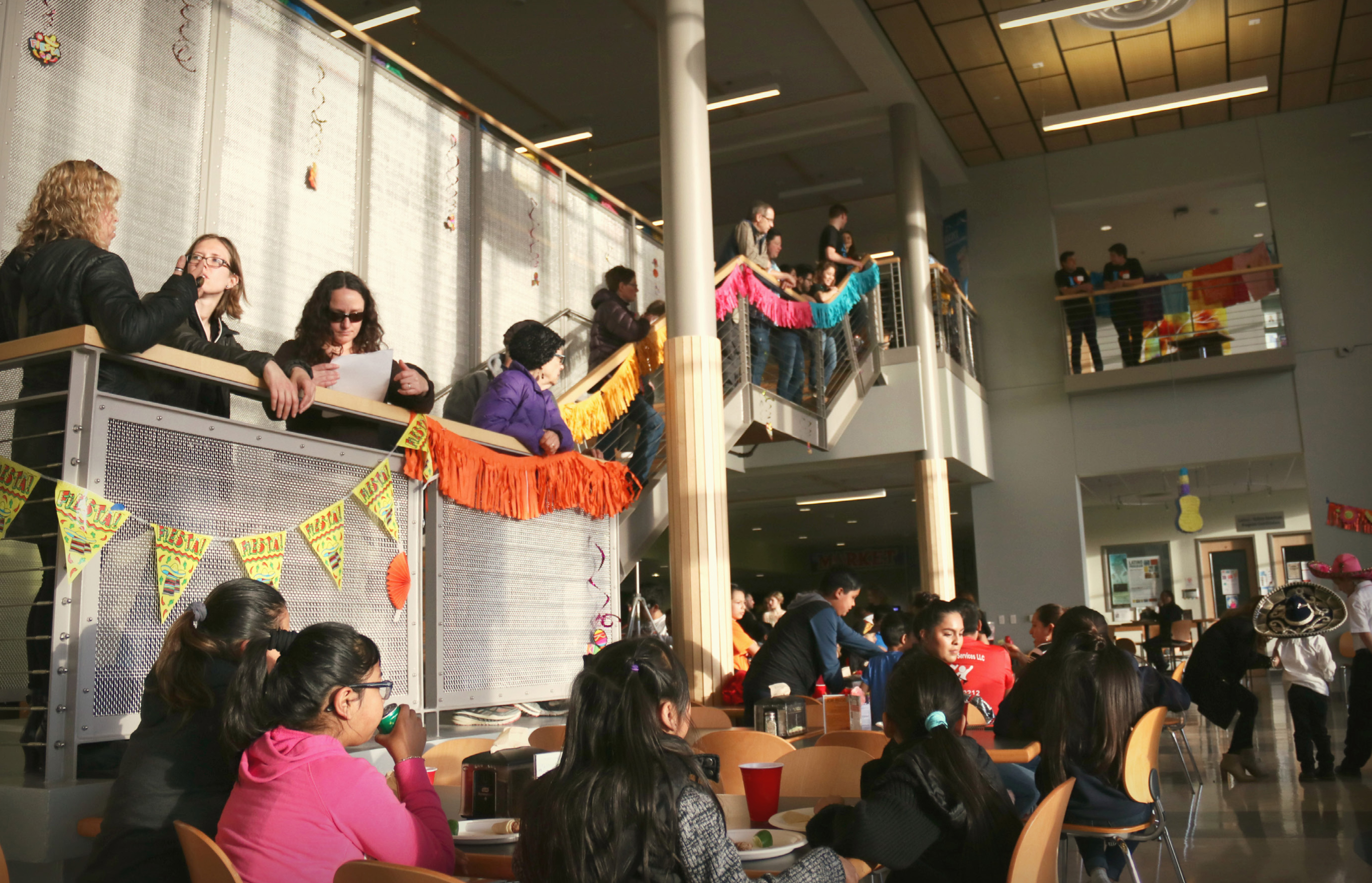 Attendees of the Latino Fiesta gather around cafeteria tables and on the stairs of the Campus Center to watch the dance performances.